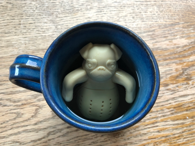 Funny image of pig-shaped tea strainer in mug, relaxing.